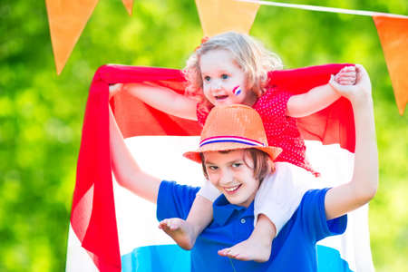 whistling: Two Dutch children, teenager boy and funny little girl, celebrating national holiday of Netherlands playing in a garden decorated with Holland and Oranje flags