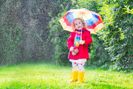 Funny cute curly toddler girl wearing red waterproof coat and yellow rubber boots holding colorful umbrella playing in the garden by rain and sun weather on a warm autumn or summer day photo
