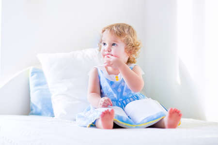 toddler playing: Cute toddler, adorable curly little girl in a blue dress, sitting on a bed reading a book playing in a sunny white bedroom