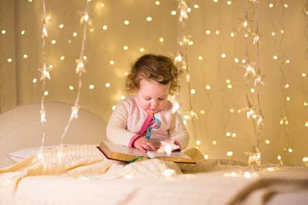 buonanotte: Carino piccolo bambino ragazza che legge un libro in una stanza buia con le luci di Natale
