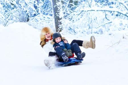 Jonge gelukkige moeder en haar schattige zoon plezier samen op een slee in een besneeuwde park Stockfoto