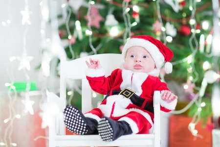 Smiling newborn baby boy in Santa costume sitting in a white rocking chair next to a beautiful Christmas tree photo