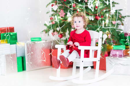 Cute curly toddler girl in a red dress relaxing in a white rocking chair under a Christmas tree between colorful present boxes photo