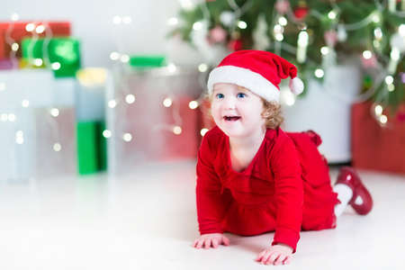 Laughing happy baby girl in a red dress and Santa hat playing between colorful Christmas presents next to a decorated tree with soft lights photo