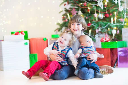 Three happy children - cute boy, his toddler sister and a newborn baby - sitting under a beautiful Christmas tree photo