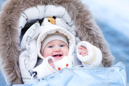 幸せな笑い赤ちゃん女の子白いジャケットと帽子を着て羊フードで暖かいベビーカーに座って、雪に覆われた冬の公園で散歩を楽しんで