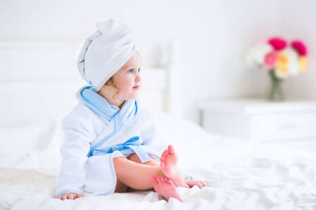 after bath: Cute curly little girl in a white and blue bathrobe with a towel over her wet hair siting in a sunny bedroom after shower or bath