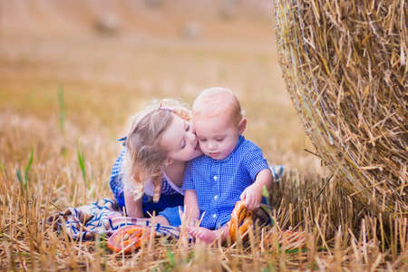 farm girl: Two children, funny curly toddler girl and a little baby boy, wearing tradtional German costumes playing in a field with hay rolls eating pretzels during Oktoberfest in Germany. Sister kissing and hugging her little brother Stock Photo