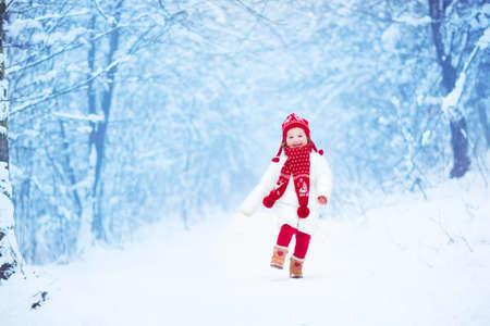 Gelukkig lachende peuter meisje gekleed in een witte donsjack en rode gebreide muts en sjaal spelen en lopen in een prachtige besneeuwde winter park op eerste kerstdag