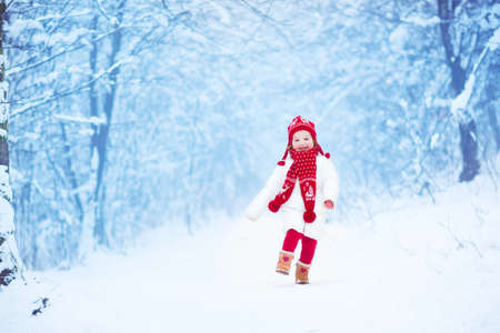 Happy laughing toddler girl wearing a white down jacket and red knitted hat and scarf playing and running in a beautiful snowy winter park on Christmas day