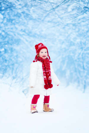 Happy laughing toddler girl wearing a white down jacket and red knitted hat and scarf playing and running in a beautiful snowy winter park on Christmas day photo