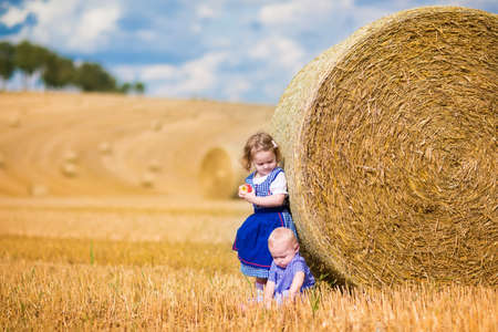 farm boys: Two children, funny curly toddler girl and a little baby boy, wearing traditional German costumes playing in a field with hay rolls eating pretzels during Oktoberfest in Germany