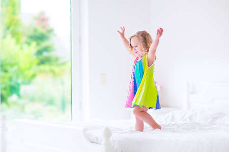child in bed: Cute little curly toddler girl in a colorful dress jumping on a big white bed laughing and having fun on a sunny weekend morning in a bedroom