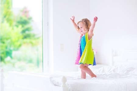 Schattig klein krullend peuter meisje in een kleurrijke jurk springen op een groot wit bed lachen en plezier op een zonnig weekend 's ochtends in een slaapkamer