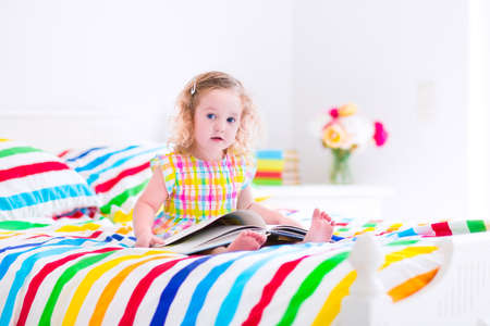 Cute curly little toddler girl reading a book sitting in a sunny bedroom on a wooden white bed with colorful rainbow bedding enjoying a nice weekend morning photo