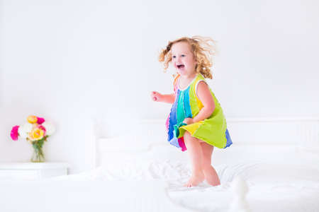 sleepover: Cute little curly toddler girl in a colorful dress jumping on a big white bed laughing and having fun on a sunny weekend morning in a bedroom