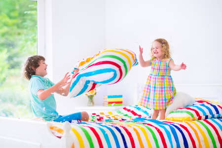 pelea: Dos ni�os, ni�o feliz riendo y ni�a rizada linda que se divierte en la lucha de almohadas con plumas en el aire saltando, riendo y riendo en un dormitorio blanco con ropa de cama colorida Foto de archivo