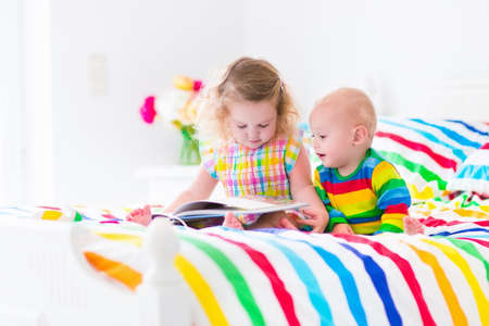 Two children, cute curly little toddler girl and a funny baby boy, brother and sister, reading a book sitting in a sunny bedroom on a wooden white bed with colorful rainbow bedding enjoying a nice weekend morning photo