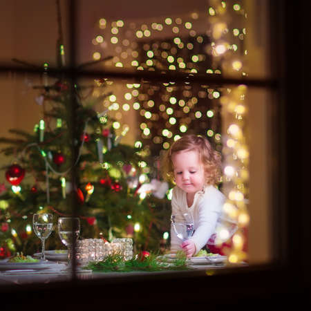 christmas dish: Cute curly toddler girl standing at a Christmas dinner table settling the dishes preparing to celebrate Xmas Eve, view through a window from outside into a decorated dining room with tree and lights