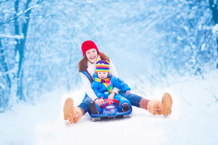 Young happy mother and her little toddler daughter enjoying a sledge ride in a beautiful snowy winter park Archivio Fotografico