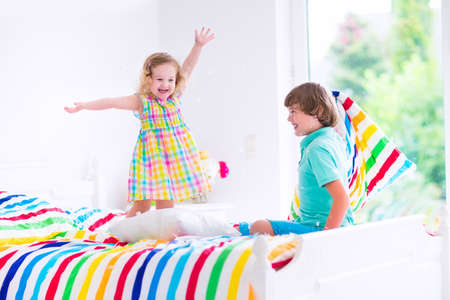 boy bedroom: Two children, happy laughing boy and cute curly little girl having fun at pillow fight with feathers in the air jumping, laughing and giggling in a white bedroom with colorful bedding