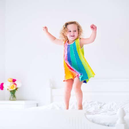 笑っている大きな白いベッドにジャンプと寝室の日当たりの良い週末の朝に楽しいカラフルなドレスでかわいい巻き毛幼児女の子
