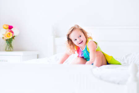 Cute little curly toddler girl in a colorful dress jumping on a big white bed laughing and having fun on a sunny weekend morning in a bedroom photo