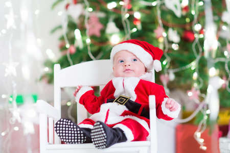 baby on chair: Little newborn baby boy in Santa outfit sitting uder a Christmas tree