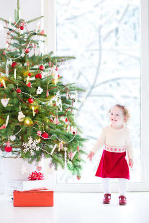 Beautiful toddler girl with curly hair wearing a red warm knitted dress playing under a Christmas tree next to a big window with a view into a snowy garden photo