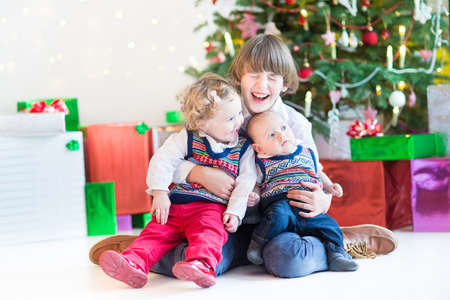 Three happy children - teenager boy, toddler girl and their newborn baby brother - playing together under a beautiful Christmas tree photo