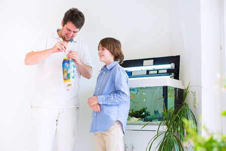 Father and son holding a plastic bag with a new fish they got in a zoo store ready to put it into a home aquarium photo
