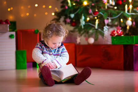 Cute curly little toddler girl in a warm knitted sweater sitting on a floor next to a Christmas tree reading a book enjoying cozy winter day at home