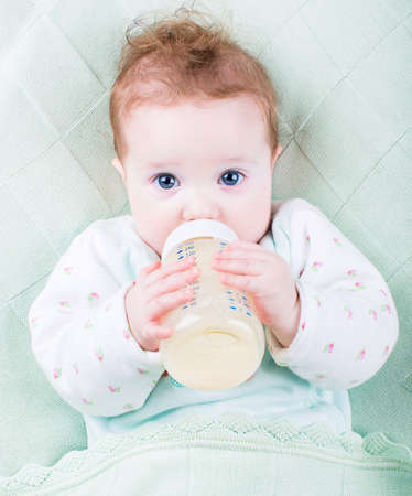 Beautiful little baby with a milk bottle under a warm knitted bl Archivio Fotografico