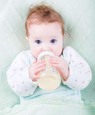 Mooie kleine baby met een fles melk onder een warme gebreide bl
