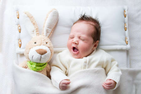 Adorable sleepy newborn baby with a toy bunny yawning in bed photo