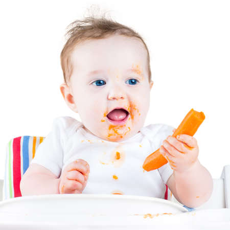 Funny laughing baby girl eating a carrot trying her first solid vegetable food sitting in a white high chair, isolated on white