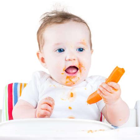 Grappig lachende baby meisje eet een wortel proberen haar eerste vaste plantaardig voedsel zit in een witte stoel, geïsoleerd op wit