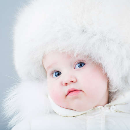 Very funny baby in a white snow suit and big fur hat photo