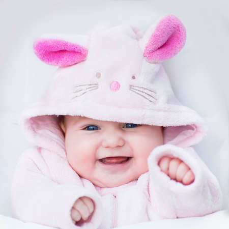 cute little girl smiling: Laughing happy baby girl sitting in a white stroller in a bunny dress-up Stock Photo