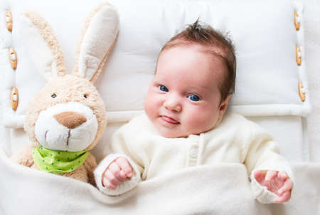 Sweet little baby girl with a toy bunny in bed