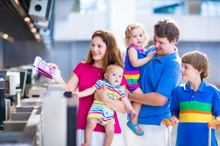 luggage airport: Big happy family with three kids traveling by airplane at Dusseldorf International airport, parents with teenager boy, toddler girl and little baby holding colorful luggage for summer beach vacation Stock Photo