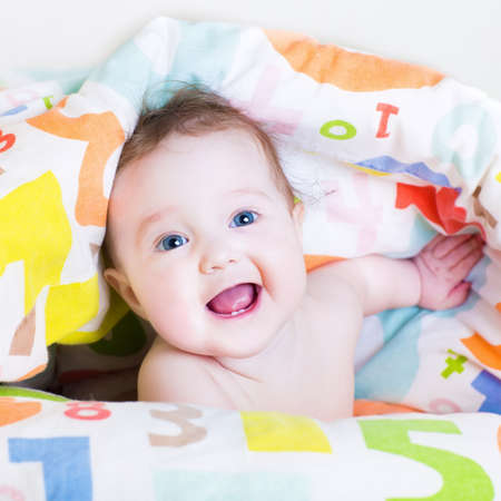Funny baby playing peek-a-boo under a colorful blanket photo