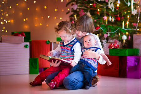 Three happy childrenm brothers and sister sitting under a Christmas tree, boy reading to a little toddler girl and funny baby photo
