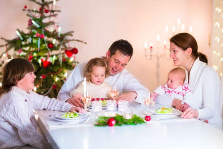 Big happy young family with three children enjoying Christmas dinner celebration, parents and kids - teen age boy, little toddler girl and baby in a dark dining room wth candles and xmas tree photo