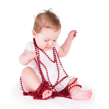 Funny baby girl playing with red pearls photo