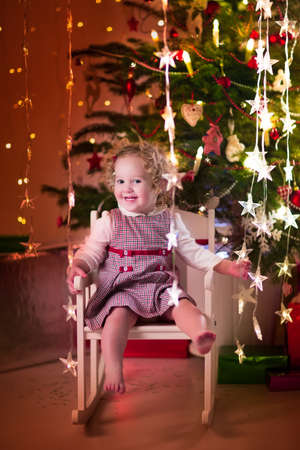 little girl dress: Cute curly little girl in a red dress playing under a Christmas tree sitting in a white rocking chair enjoying Xmas eve party at home Stock Photo