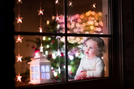 xmas: Cute curly toddler girl sitting with a toy bear at home during Xhristmas time, preparing to celebrate Xmas Eve, view through a window from outside into a decorated dining room with tree and lights Stock Photo