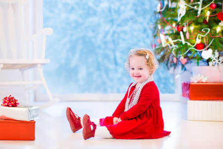 Cute curly little girl in a red dress and white pearl necklace playing under a Christmas tree with presents sitting on the floor of a white living room with rocking chair next to a window into a snowy winter garden photo