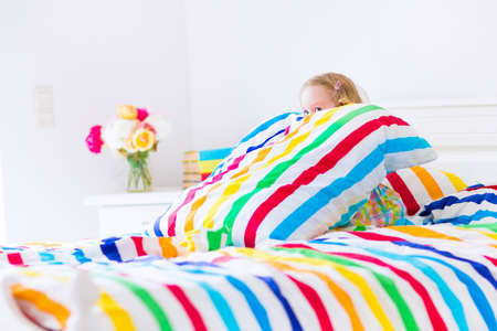 Cute funny little toddler girl sitting in a white bed with colorful rainbow stripe pillow and cover sheet playing hide and seek on a sunny morning at home