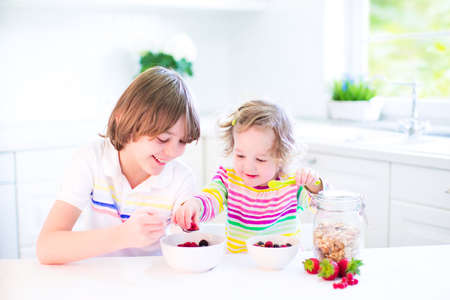 Happy teenager boy and his cute toddler sister having fruit and cereal with strawberry for breakfast before school and kindergarten drinking juice in a sunny white kitchen with a window photo